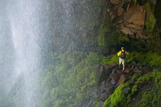 A man hiking behind a waterfall near Mount Hood OR : Stock Photo