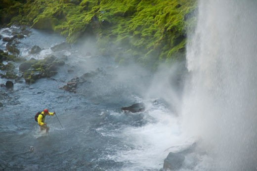 A man hiking across a stream below a waterfall near Mount Hood OR : Stock Photo