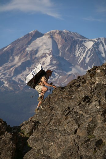 A man carrying a kitchen sink up  mountain near Mount Adams WA : Stock Photo