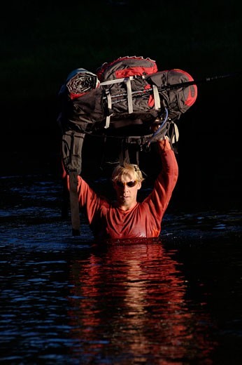 A man carrying a backpack over his head while crossing a river : Stock Photo