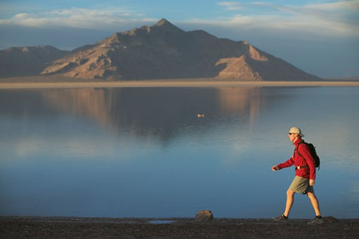 Stock Photo: 1989-1816 A man hiking on the Bonneville Salt Flats in Utah while listening to an MP3 player