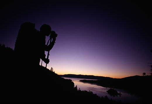 A man takes predawn photographs while hiking near Emerald Bay Lake Tahoe CA : Stock Photo