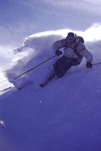 A man skiing powder snow in the Utah backcountry : Stock Photo