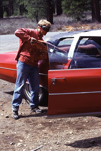 Stock Photo: 1989-2291 A man cutting the roof off a Cadillac in Truckee CA