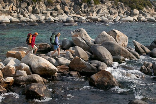 A couple hiking along the shore of Lake Tahoe CA : Stock Photo