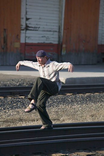 Stock Photo: 1989-2773 A man walking along and balancing on railroad tracks