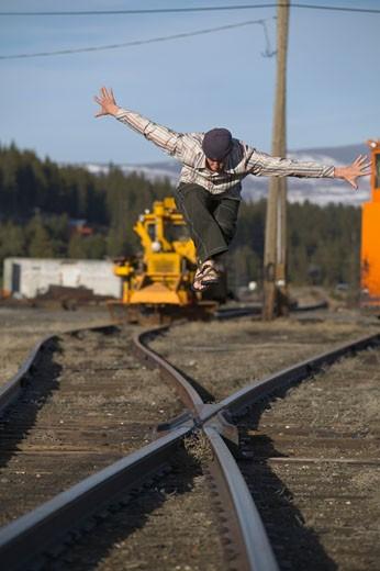 Stock Photo: 1989-2774 A man walking along and balancing on railroad tracks