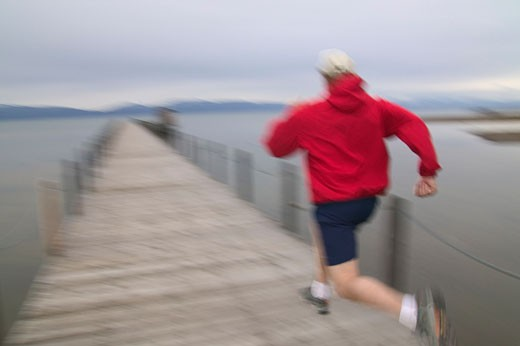 A man running on a pier on Lake Tahoe in Tahoe City CA : Stock Photo