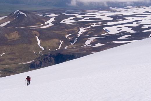 A skier climbing Mount Vsevidov in the Aleutian islands Alaska with the tundra below : Stock Photo