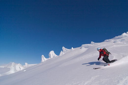 A woman skiing on a glacier on Mount Vsesevidov in the Aleutian Islands in Alaska : Stock Photo