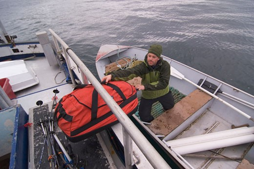 Loading equipment into a skiff in the Aleutian Islands in Alaska : Stock Photo