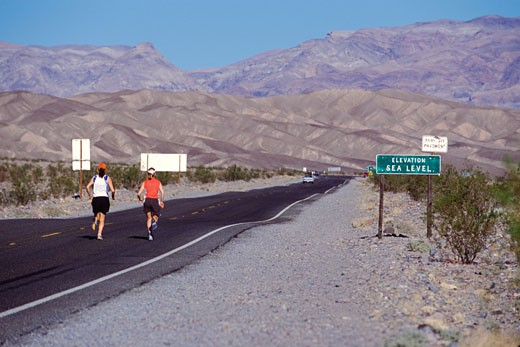 2 women running on a road in Death Valley CA : Stock Photo