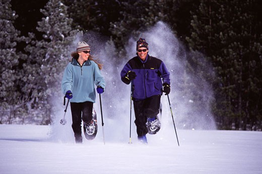 A couple running on snowshoes in powder snow in Squaw Valley California : Stock Photo