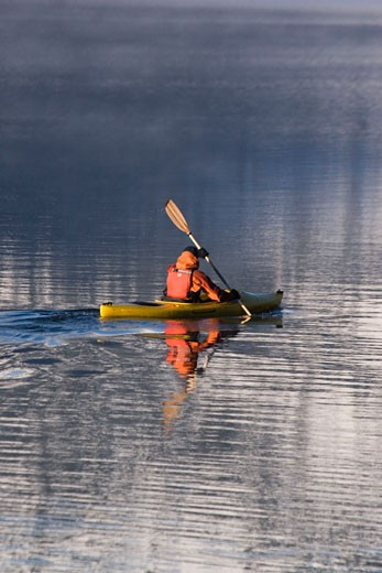 A man kayaking at dawn through mountain reflections on Donner Lake CA : Stock Photo