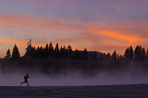 A man running along the shore of a misty lake at dawn near Truckee California : Stock Photo