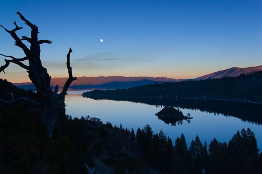 The full moon rising over Emerald Bay at sunset with alpenglow at Lake Tahoe California : Stock Photo