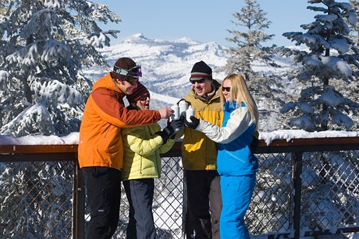 Friends smiling and drinking hot chocolate on a snowy deck in winter at Northstar ski resort near Lake Tahoe in California : Stock Photo