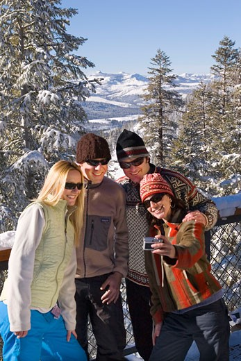 Four friends taking a group photo on the deck of a ski lodge on a snowy day at Northstar near Lake Tahoe : Stock Photo
