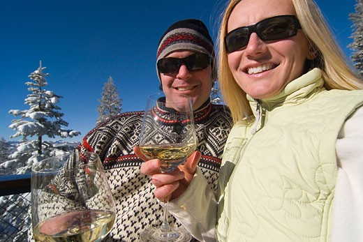 A couple drinking white wine on the deck of a ski lodge on a snowy day at northstar near Lake Tahoe : Stock Photo