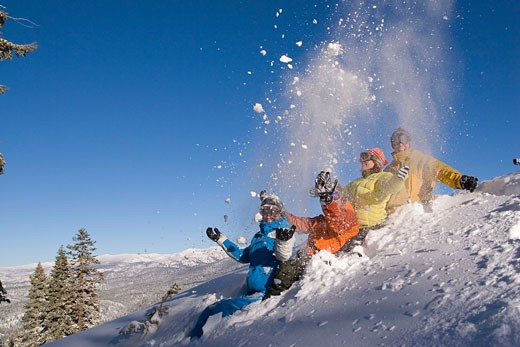 Four friends sitting in the snow throwing snow into the air at Northstar ski resort near Lake Tahoe California : Stock Photo