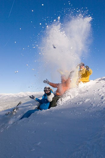 Stock Photo: 1989-4032 Four friends sitting in the snow throwing snow into the air at Northstar ski resort near Lake Tahoe California