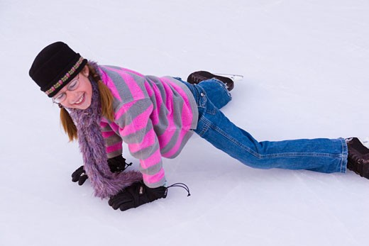 Stock Photo: 1989-4148 A smiling young girl lying on the ice at a skating rink at Northstar ski resort near Lake Tahoe California