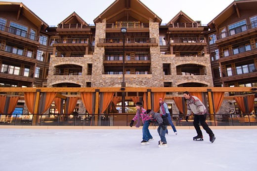 A family ice skating at Northstar ski resort near Lake Tahoe in California : Stock Photo