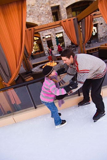 A father holding out his arms for his daughter as she skates towards him at Northstar ski resort near Lake Tahoe in California : Stock Photo
