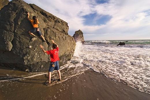 Stock Photo: 1989-4424 A man and a woman rock climbing next to the Pacific Ocean at Mickeys Beach near Stinson Beach in California