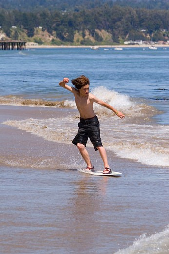 A young boy skim boarding on the beach on the Pacific Ocean in Santa Cruz California : Stock Photo
