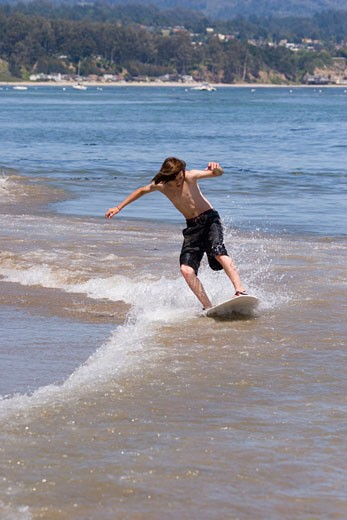Stock Photo: 1989-4437 A young boy skim boarding on the beach on the Pacific Ocean in Santa Cruz California