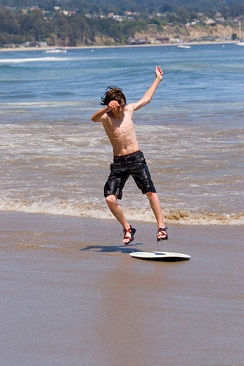 Stock Photo: 1989-4443 A young boy skim boarding on the beach on the Pacific Ocean in Santa Cruz California