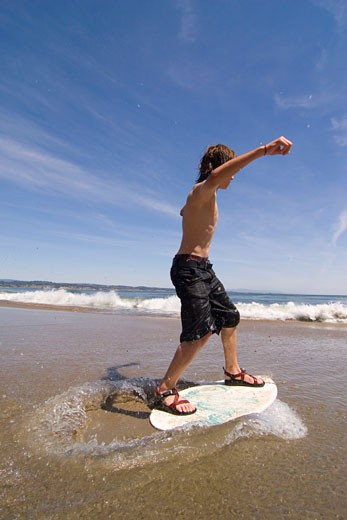 Stock Photo: 1989-4451 A young boy skim boarding on the beach on the Pacific Ocean in Santa Cruz California