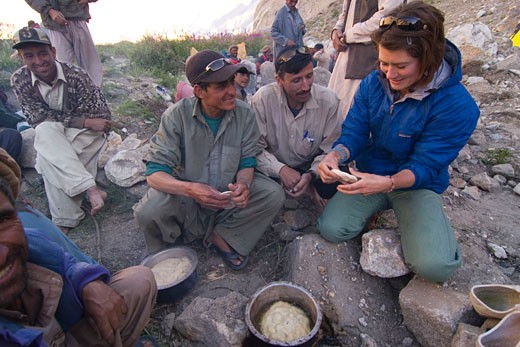 Stock Photo: 1989-4571 A caucasian woman making chapati bread with some Balti men in Pakistan
