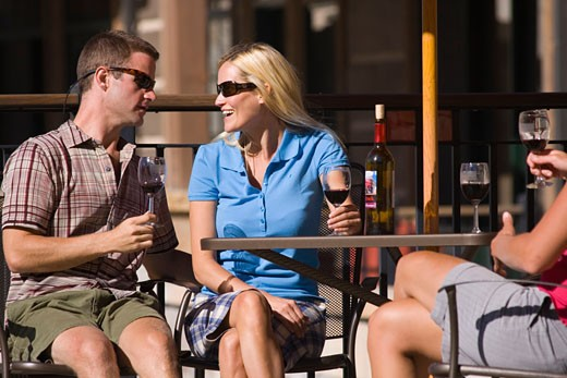 A happy couple smiling and drinking wine at Northstar ski resort near Lake Tahoe in California : Stock Photo