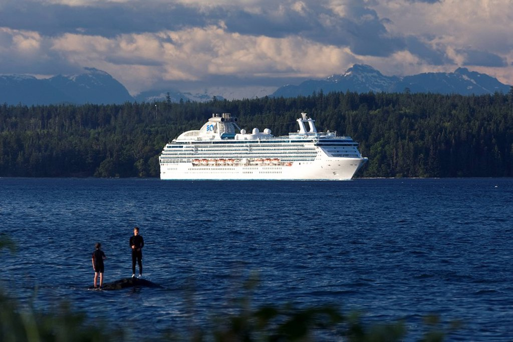 Two boys fishing while a Cruise Ship enroute to Vancouver passes thru Discovery Passage, Campbell River, Vancouver Island, British Columbia, Canada : Stock Photo
