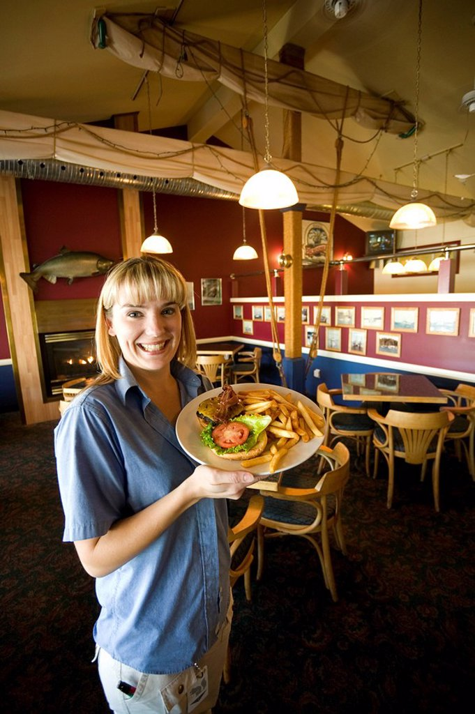 Female server at the Quarterdeck Pub with a hamburger platter  Port Hardy, Vancouver Island, British Columbia, Canada : Stock Photo