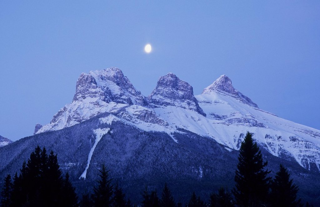 Moon rising over the Three Sisters Mountains at dusk, Canmore, Alberta, Canada : Stock Photo