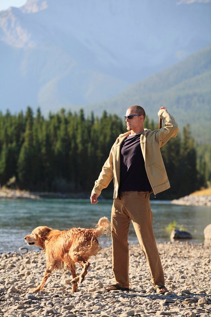 Stock Photo: 1990-11656 Young man plays fetch with his dog by a river in the mountains, British Columbia, Canada