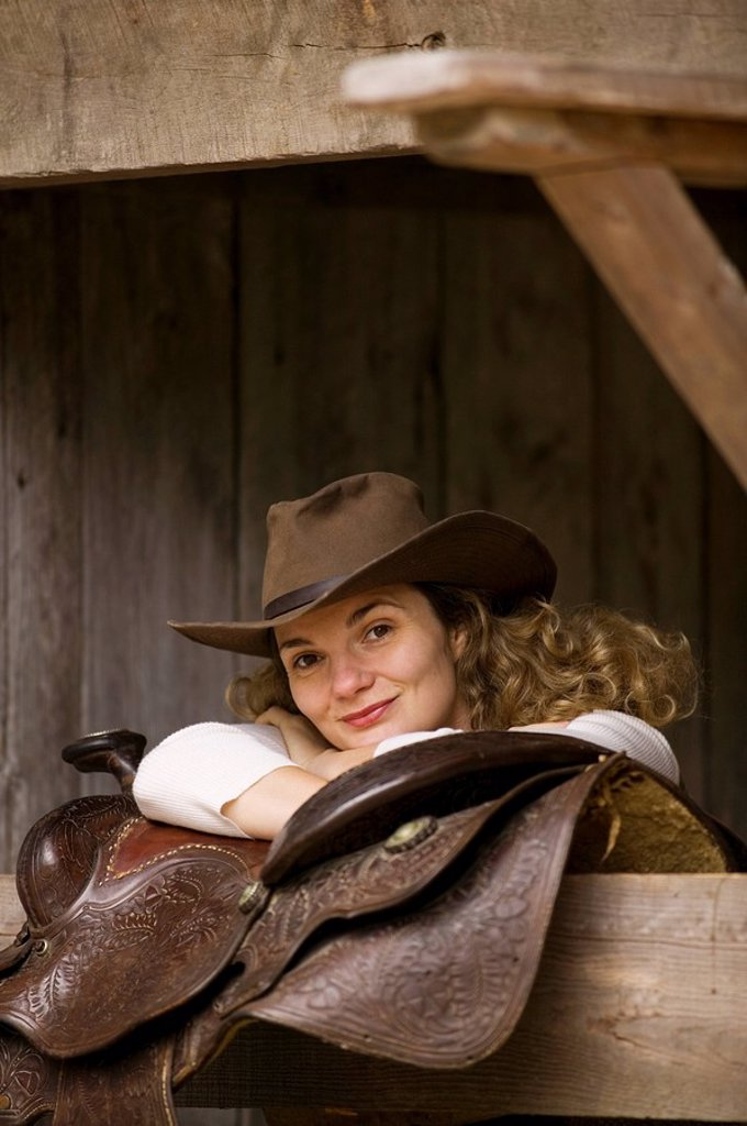 thirty-one year old blond woman wearing a cowboy hat and horse saddle, Val des Monts, Quebec, Canada : Stock Photo