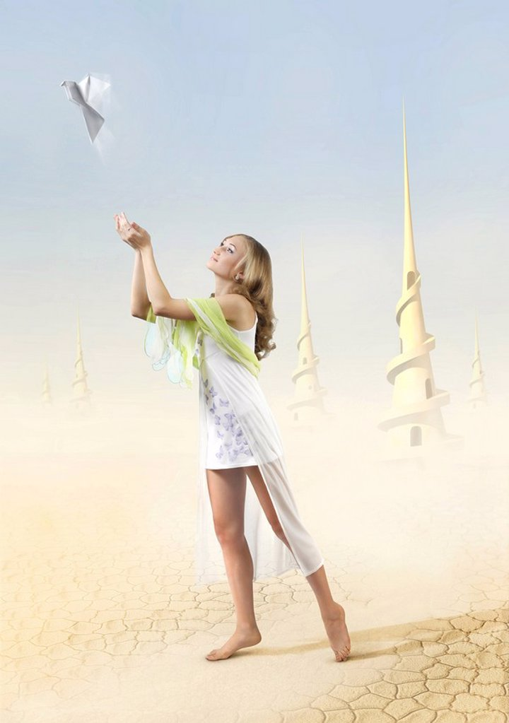 Digital photo-illustration of a Young beautiful girl in a fantastic extraterrestrial desert world covered with sand and dust and high spiral towers in the background The girl is releasing a white paper peace dove into blue sky : Stock Photo