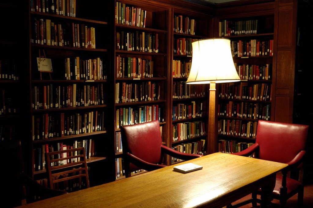 Shelves full of books in a cosy library corner with two empty chairs and a lamp at night University of Toronto Canada Fiction section in Hart house library : Stock Photo