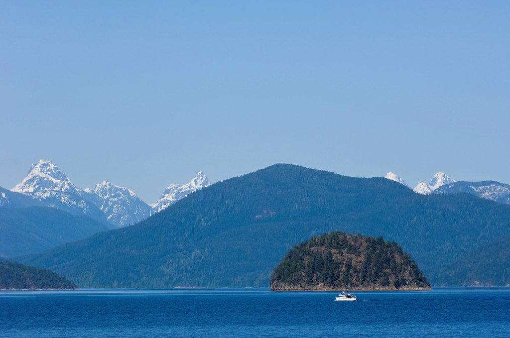 View eastward from Cortes Island to Coast Range mountains with small fishing boat in the distance, British Columbia, Canada : Stock Photo