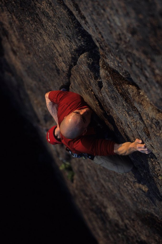 Stock Photo: 1990-14782 A focused climber leading a gear route called Inhuman Eraser 5.10, Welsford, New Brunswick, Maratimes, Canada