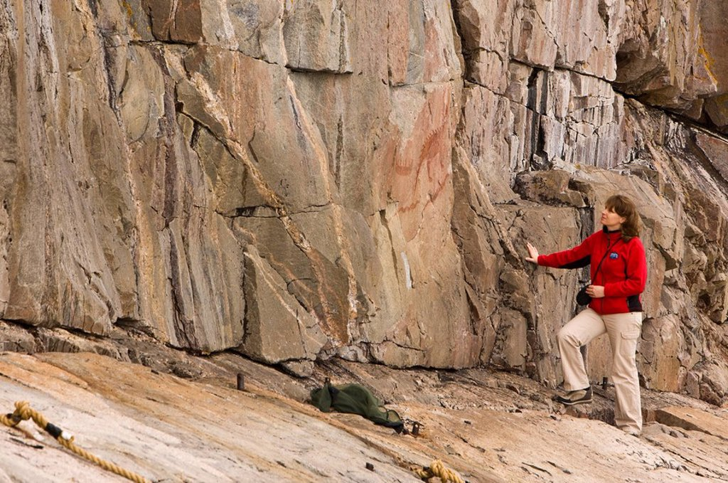 Tourist viewing the ancient pictographs on Agawa Rock, Agawa Rock Pictographs Trail, Lake Superior, Lake Superior Provincial Park, Ontario, Canada : Stock Photo
