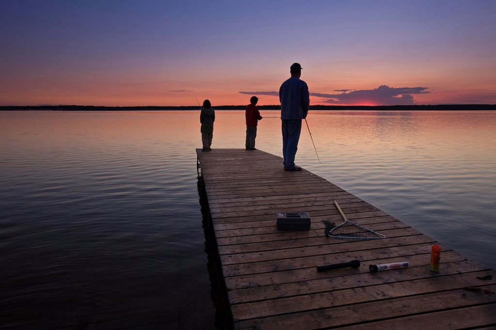 A father with his two sons fishing at the end of a wharf on Lake Audy at sunset, Riding Mountain National Park, Manitoba, Canada : Stock Photo