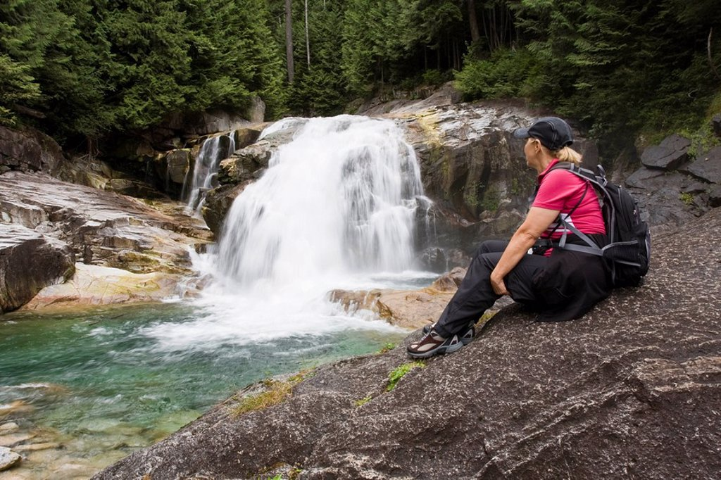 Woman hiker sitting on rock looking at waterfalls in Golden Ears Provincial Park in Maple Ridge, British Columbia, Canada : Stock Photo