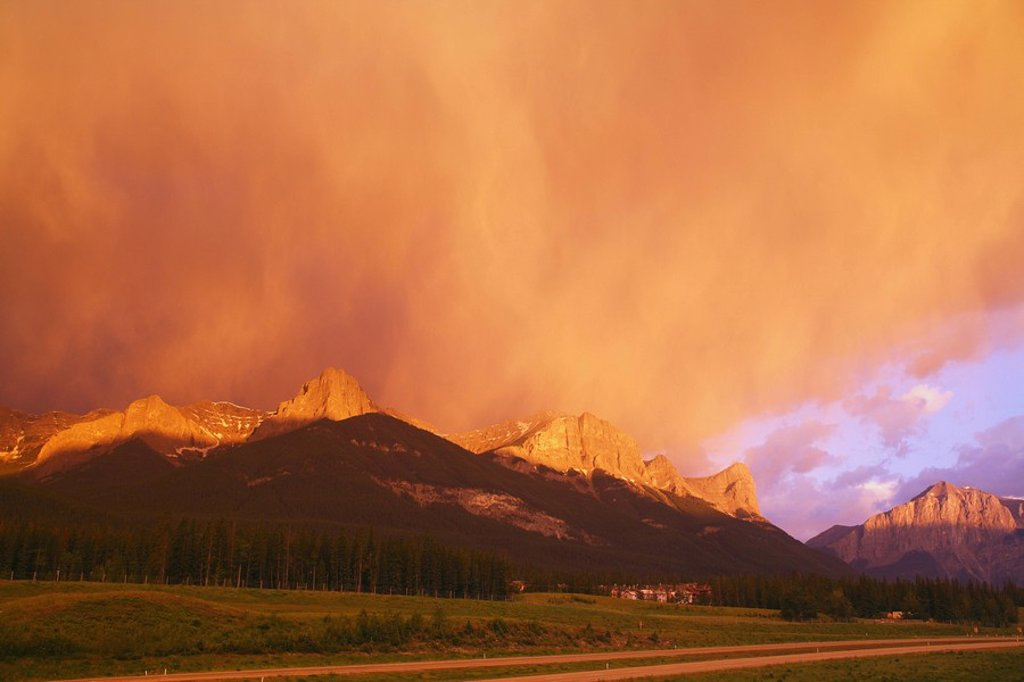 A spectacular sunrise lights up a giant storm cloud over Ha Ling Peak, the Bow Valley and the Trans_Canada Highway in Canmore, Alberta, Canada : Stock Photo