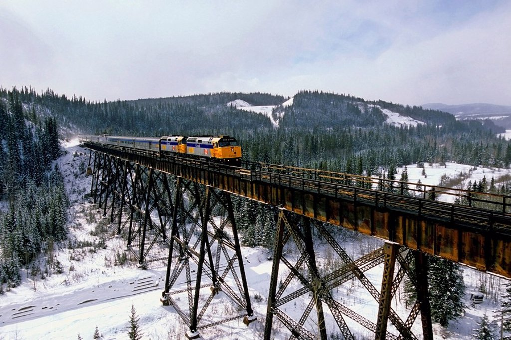 Stock Photo: 1990-18143 A Via Rail passenger train crossing a steel tressel in the foothills of Alberta Canada.