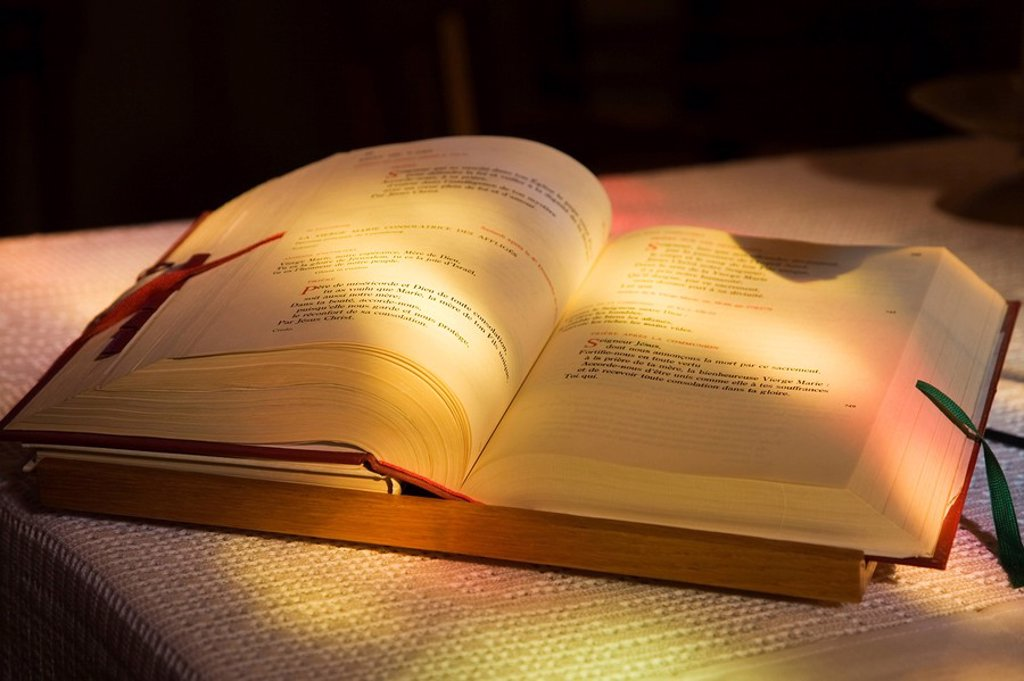 Stock Photo: 1990-19420 Sunlight shining through a stained glass window onto an opened French language Prayer book on an altar table. Saint_Francois_de_Sales Church, Laval, Quebec, Canada